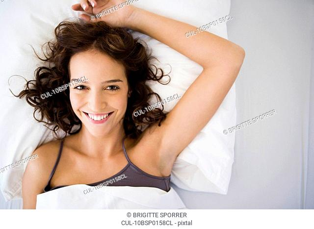Young woman in bed smiling to camera