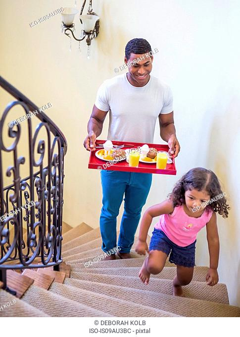 Father and daughter walking up stairs carrying breakfast on tray