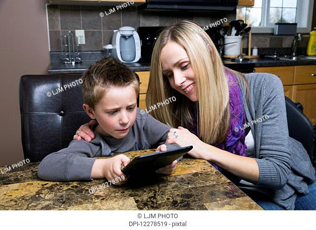 Disabled mother helping her son learn on a tablet; Spruce Grove, Alberta, Canada