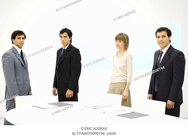 Business associates standing around conference table, looking at camera