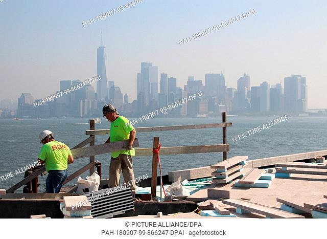 06 September 2018, USA, New York: Construction workers are working on the new museum under construction on Liberty Island, the island in the harbour of New York