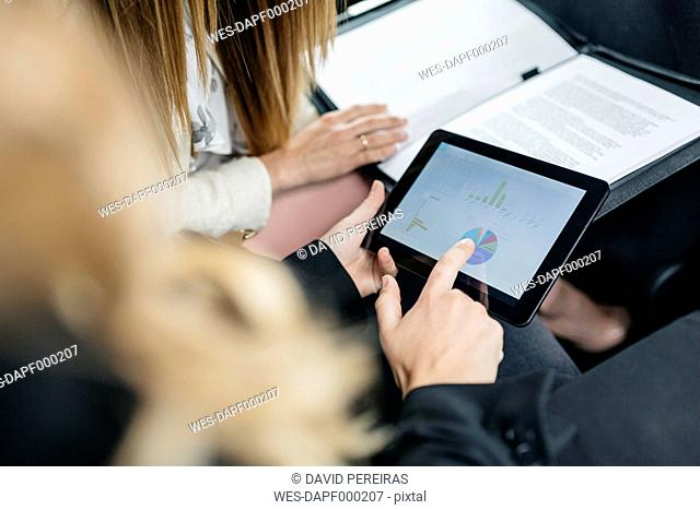 Two businesswomen with digital tablet and documents working in car