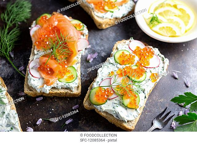 Bread topped with cream cheese, salmon, cucumber, radish and caviar