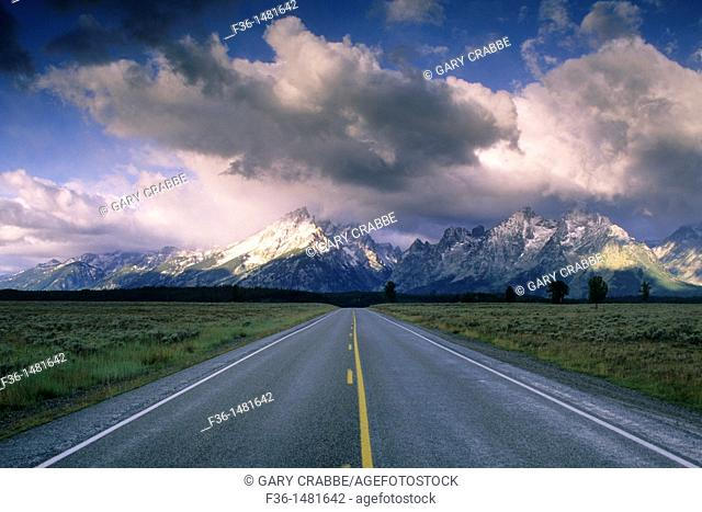 Straight road below mountain range dusted by first snow of fall, Grand Teton National Park, WYOMING