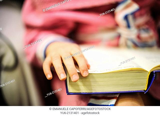 Child's hand while turning the page of the book