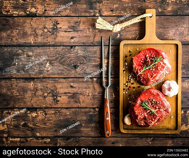 Raw marbled meat steak Filet Mignon with seasonings, fork, wooden cutting board. Space for text. Beef steak ready for cooking. Top view. Ingredients