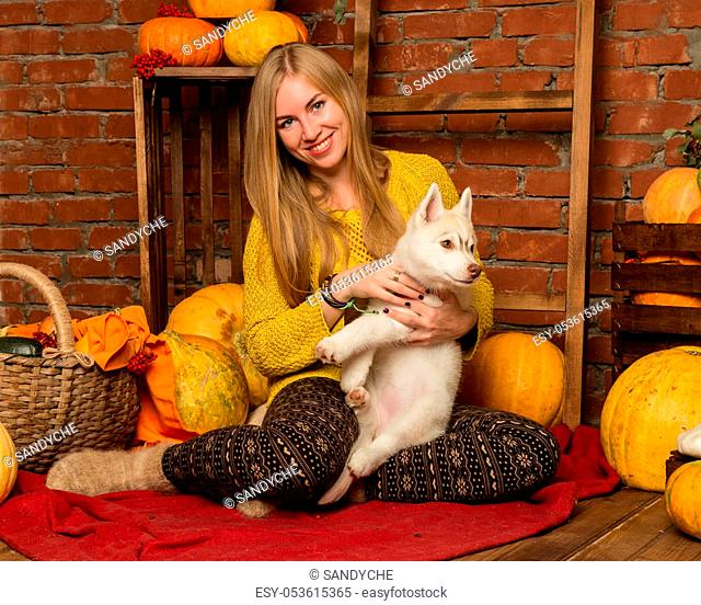 happy beautiful woman with husky puppy with autumn harvest on a brick wall background