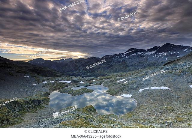Clouds at dawn are reflected in Lai Ghiacciato framed by peaks Val Ursaregls Chiavenna Valley Valtellina Lombardy Italy Europe
