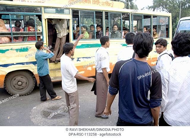 Street scene ; man calling for passengers for bus public transport in Dhaka ; Bangladesh