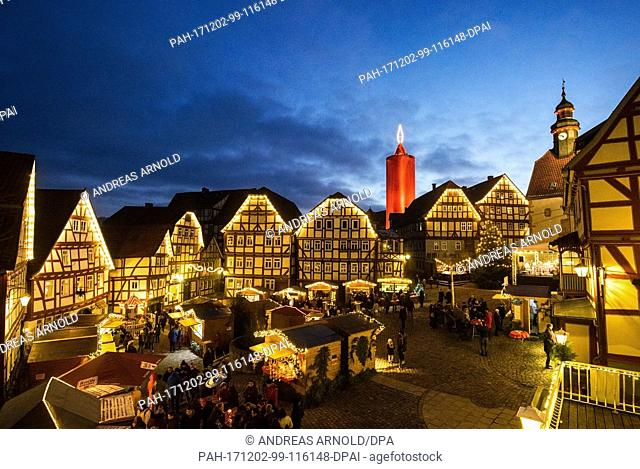 dpatop - The world's largest candle shines at the Christmas market in Schlitz, Germany, 02 December 2017. A 36 metre high stone tower is wrapped in a red cloth...