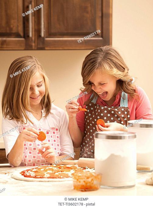 Two girls 10-11 preparing pizza in kitchen