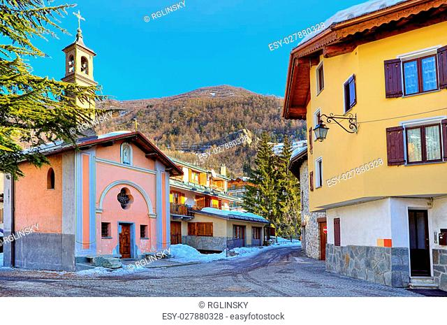 Small town square surrounded by typical houses and chapel in popular tourist ski resort of Limone Piemonte in Italy