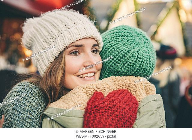 Happy woman hugging a friend on the Christmas Market