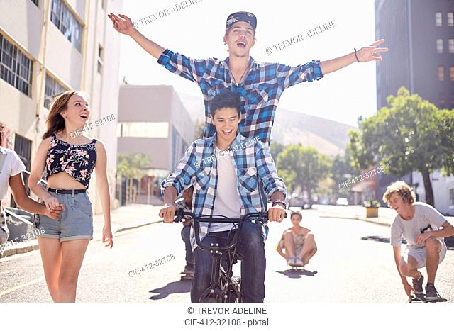 Teenage friends riding BMX bicycle and skateboarding on sunny urban street