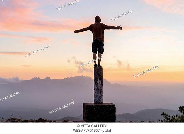 Spain, Barcelona, Natural Park of Sant Llorenc, man standing on pole at sunset