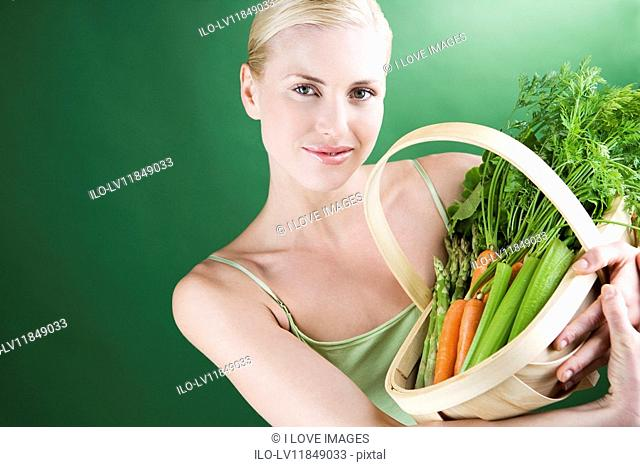 A young woman holding a basket full of vegetables, smiling