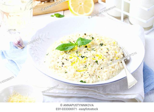 Risotto with lemon and fresh basil on a white wooden background