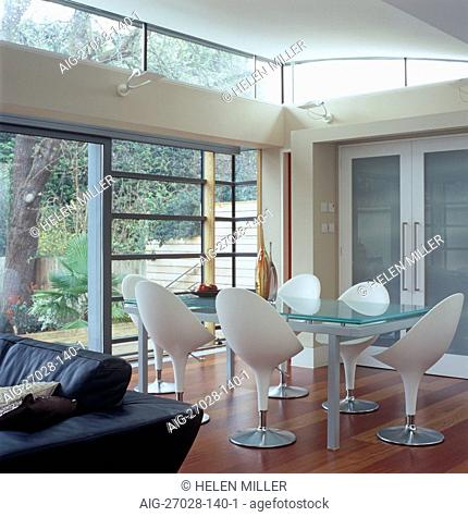 Glass table and retro style chairs behind leather sofa in open plan room