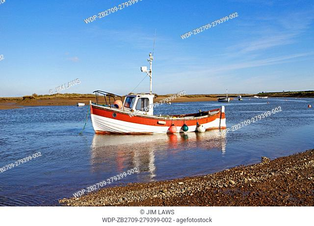 A view of an inshore fishing boat anchored in the harbour at Burnham Overy Staithe, Norfolk, England, United Kingdom