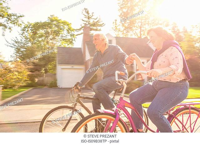 Romantic senior couple holding hands cycling along suburban road