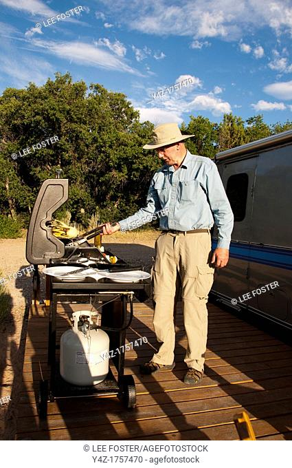 USA, Utah, grilling dinner at classic Airstream travel trailers available as lodging at the Shooting Star Drive-In in Escalante