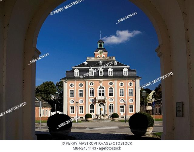 Pink with black roof and white trim Baroque architectural style building through arch, Bruchsal, Germany