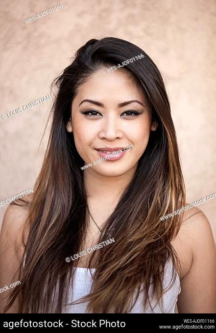 Smiling beautiful young woman against wall