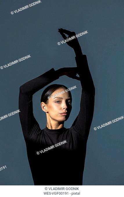 Portrait of woman dressed in black with flare on her face doing stretching exercise
