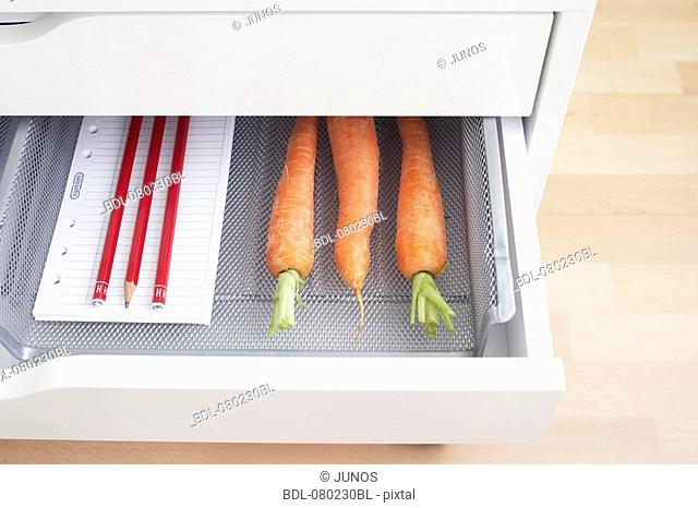 view into open desk drawer containing carrots and pencils