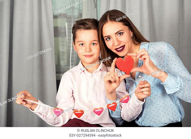 Happy Valentines Day or Mother day. Young boy spend time with her mum and celebrate with gingerbread heart cookies on a stick
