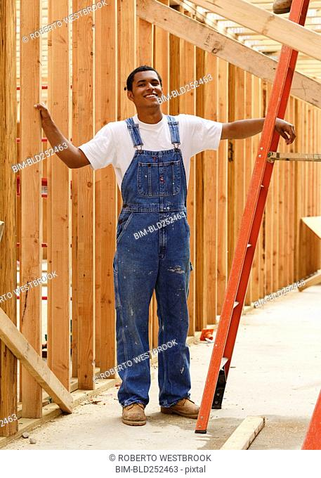Portrait of smiling mixed race man leaning on ladder at construction site