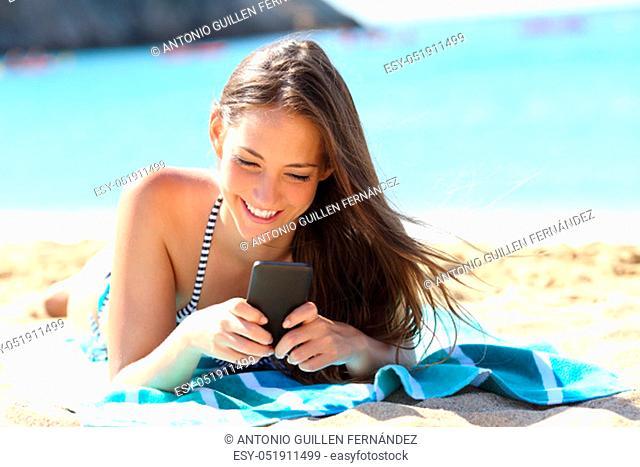 Happy girl in bikini using smart phone lying on a towel on the beach on summer vacation