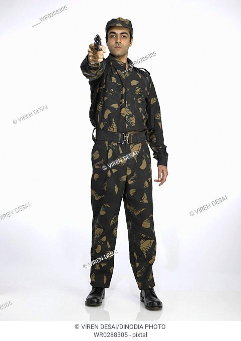Indian army soldier standing in relaxed position aiming handgun MR702A