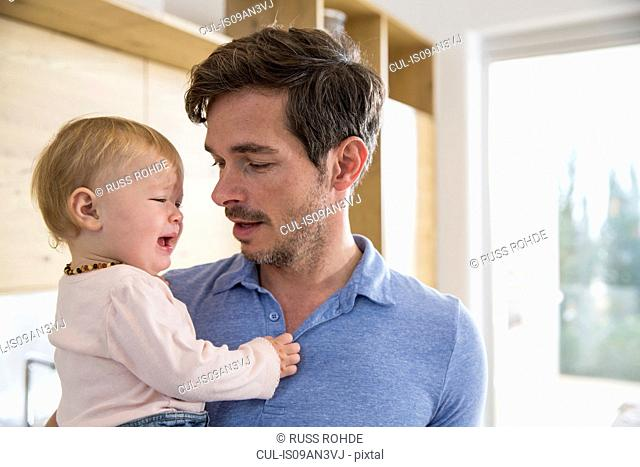 Female toddler crying in fathers arms in kitchen
