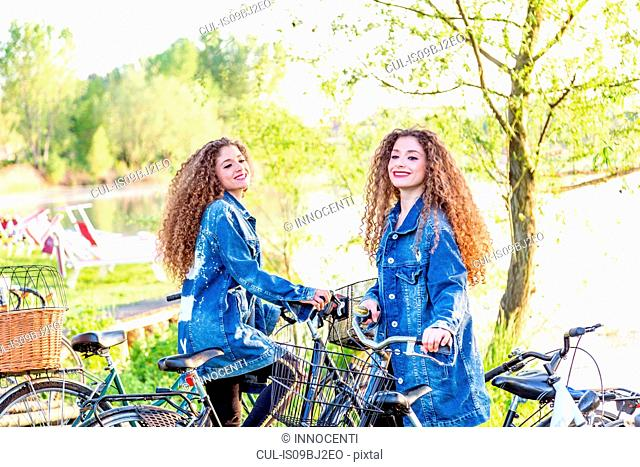 Fashion blogger twins with pushbikes by lake, Mantova, Lombardia, Italy