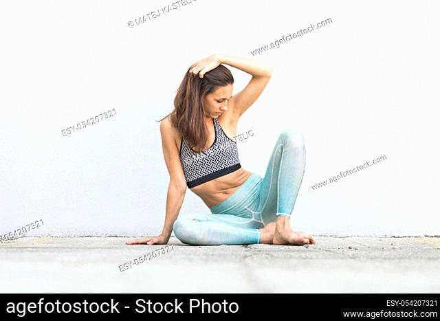 Fit sporty active girl in fashion sportswear sitting on the floor in front of gray wall. Outdoor sports, active urban lifestyle concept