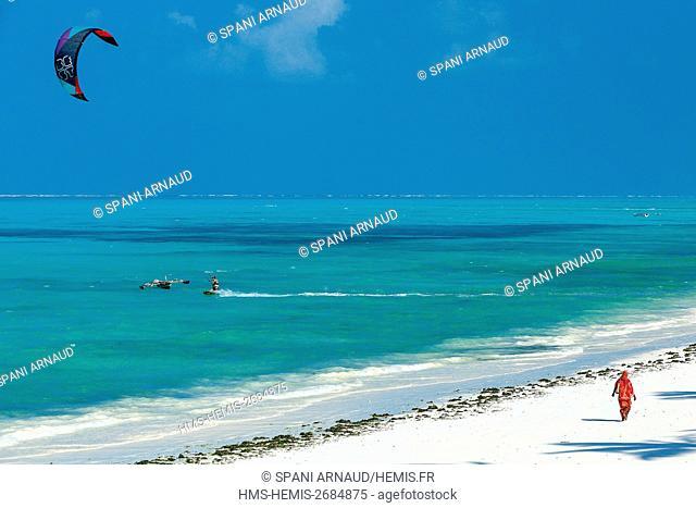 Tanzania, Zanzibar, Jambiani, veiled woman walking on a white sandy beach lapped by turquoise waters