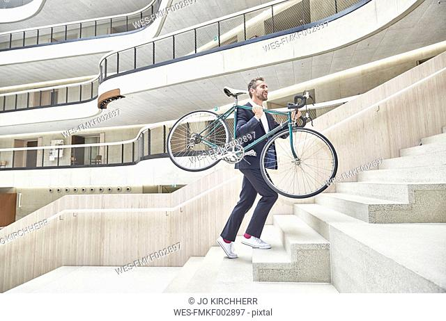 Businesssman carrying bicycle in modern office building