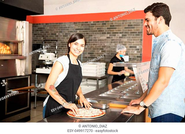 Handsome customer smiling looking at chef while woman in black apron preparing pizza and looking at camera and smiling