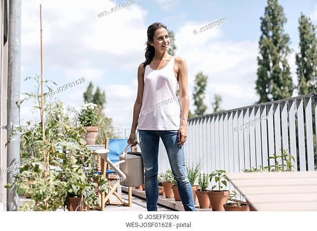 Smiling woman on balcony holding watering can