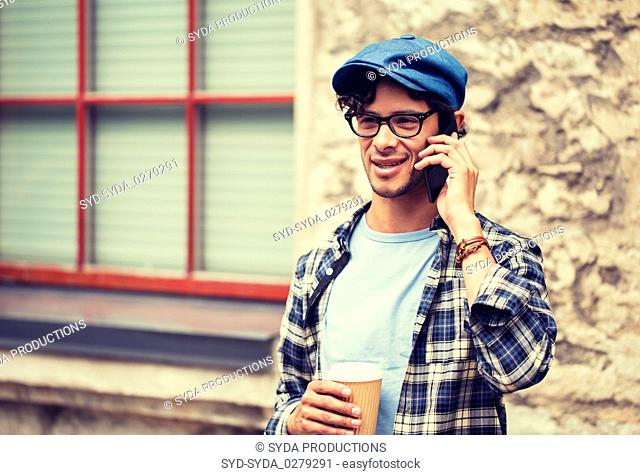 man with coffee calling on smartphone in city