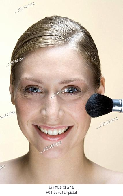 A woman applying face powder