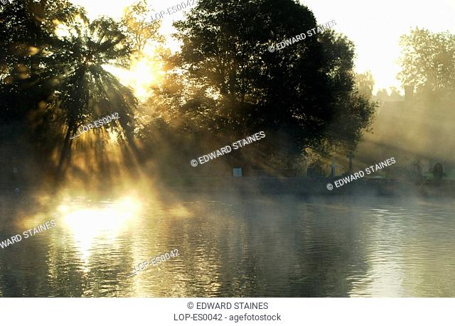 England, Buckinghamshire, Bisham, Sunrays through the mist at Bisham, with churchyard in background. Bisham is home to one of the Sport England's National...