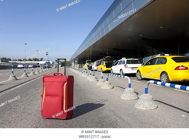 Rolling Luggage Outside an Airport Terminal