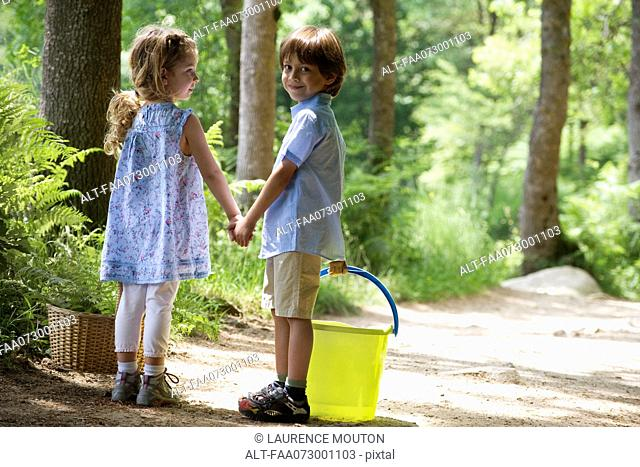 Children holding hands on path in woods