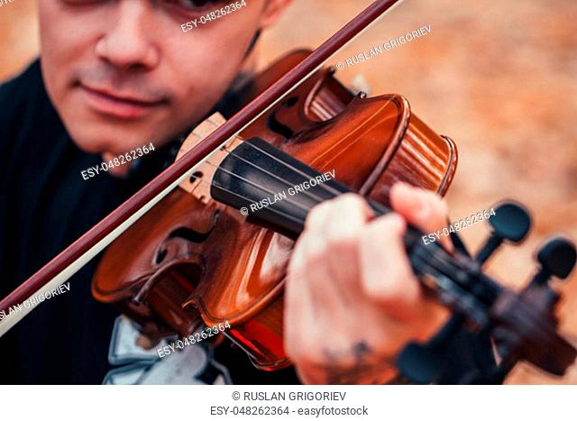 young man playing violin in the autumn forest