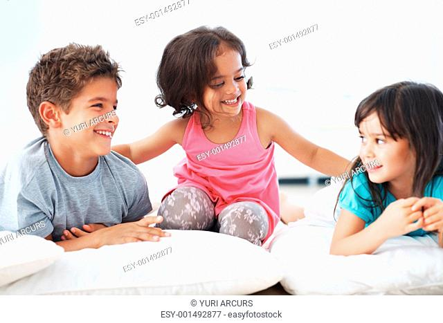 Portrait of three beautiful children smiling lying on floor together