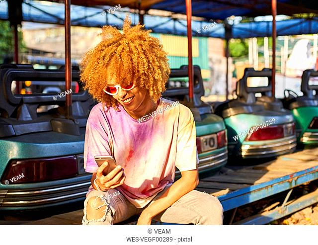 Smiling woman using cell phone at bumper car on a fair