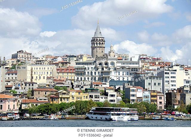 Bosphorus in front of buildings in city against sky