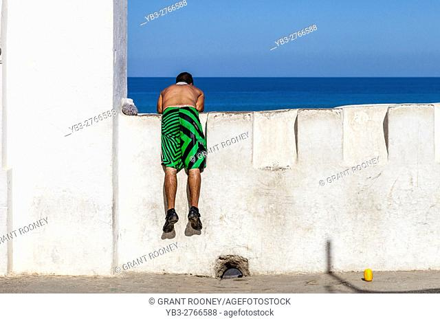 A Young Man In Swim Wear Looks Over A Wall Onto The Beach, Asilah, Morocco